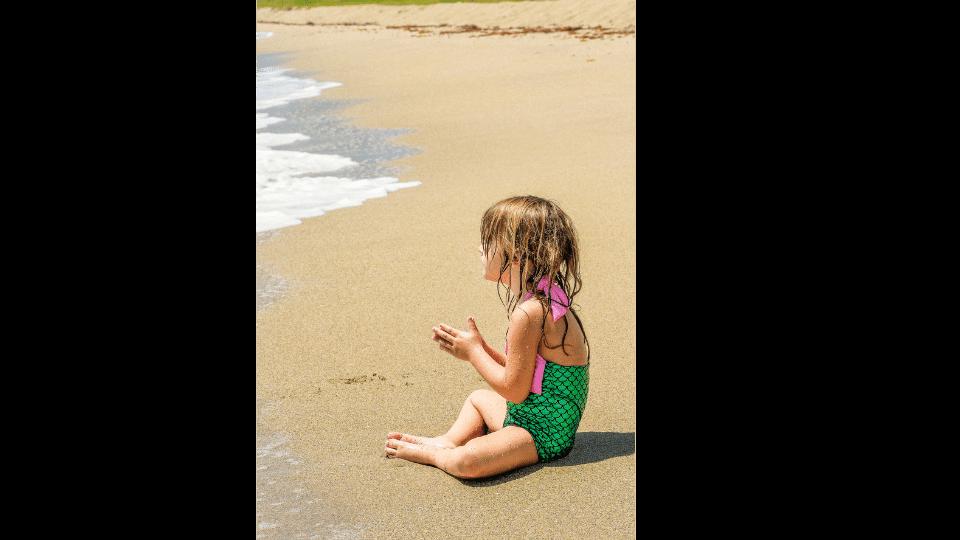 petite fille assise sur la plage en maillot sirene