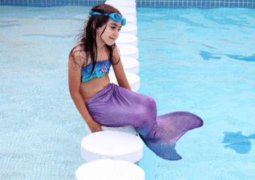 petite fille au bord de la piscine avec maillot de bain sirene