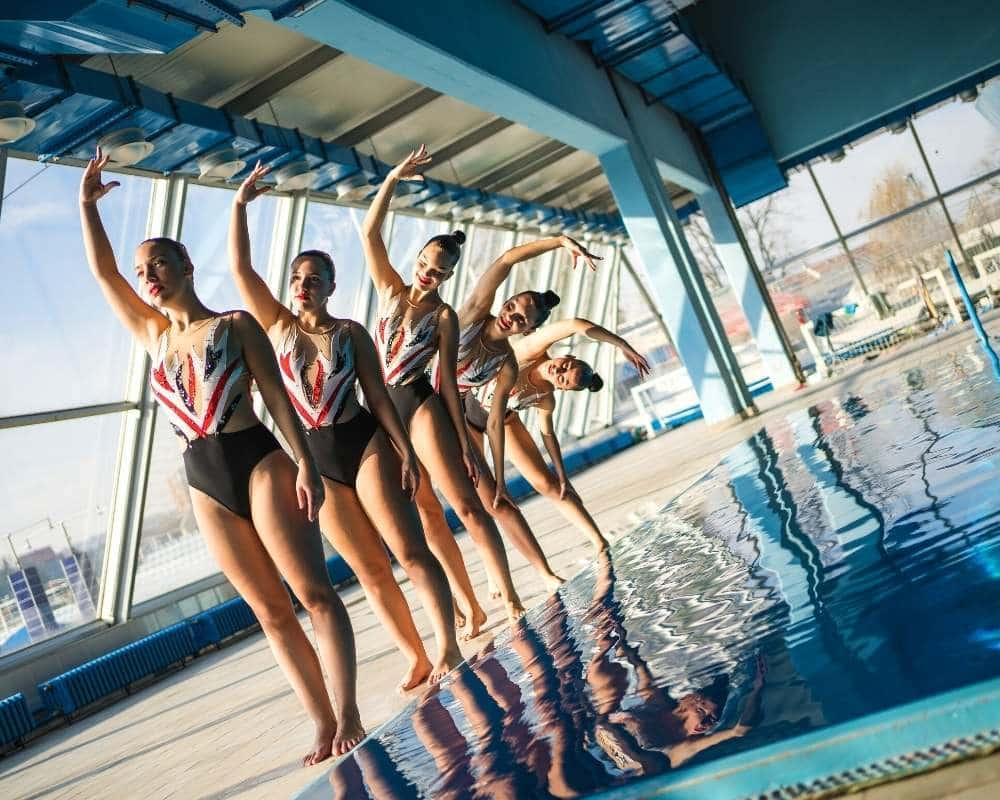 compétitrices de natation synchronisée sur le bord du grand bassin